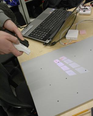 Ning Li + ET Christian Zickenrott,  Pengfei Dong u. Tao Wang | Mobile Pico Projection  Im Masterraum des Fachbereiches Design hat jeder Masterstudent eine eigene Box um dort Werkzeug oder private Utensilien abzulegen. Mitunter kann diese Box sehr voll und unübersichtlich sein bzw. es können sich verschiedene Projektarbeiten darin befinden. Um schnell einen Überblick über die jeweiligen Boxen und deren Inhalt zu erhalten, wurden verschieden Zoomstufen genutzt.  http://vimeo.com/18632744