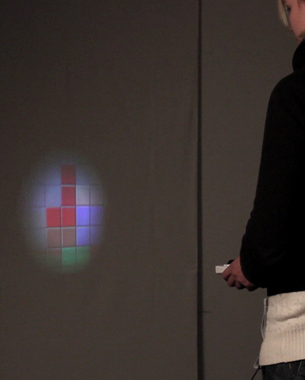 Sascha Reinhold | Mobile Pico Projection  Bei DarkTris handelt es sich um eine Variante des Spieleklassikers Tetris, welche auf einer Wand gespielt werden kann. Dabei sieht der/die Spieler_in immer nur einen Ausschnitt des Spielfeldes, das wie mit einer Taschenlampe beleuchtet wird. Durch Bewegung des Controllers lassen sich weitere Teile des Spielfeldes einsehen. Am oberen Rand erscheinen regelmäßig neue Spielsteine, die dann geschickt unter einer festgelegten horizontale Grenze platziert werden müssen. Das Aufnehmen und Ablegen geschieht über Gesten mit dem Controller. Ziel ist es, möglichst viele Spielsteine im Spielfeld abzulegen.