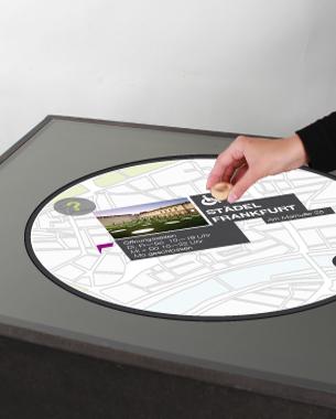 Katharina Herzog | Finden statt Suchen  explORT ist ein Orientierungs- und Erinnerungstool für den städtischen Raum.  Es besteht aus einer Homestation, einem Armband zur Navigation und öffentlichen Tabletop-Displays, die rasterartig in der Stadt verteilt sind. Das Armband navigiert den Nutzer durch die Stadt und es können gleichzeitig Lieblingsorte mit diesem gesammelt werden, die zu einer individuellen Erinnerungs-Map zusammengefügt werden.  Der Nutzer interagiert mit den Displays, ausschließlich über tangible Objekte, durch diese Orte spielerisch gesucht oder wieder in Erinnerung gerufen werden können.